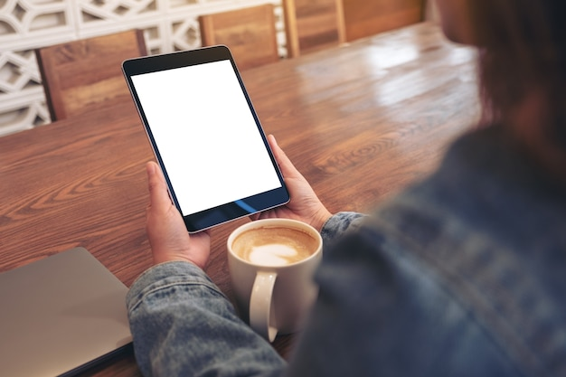 Mockup afbeelding van een vrouw met zwarte tablet pc met leeg wit scherm met koffiekopje en laptop op houten tafel