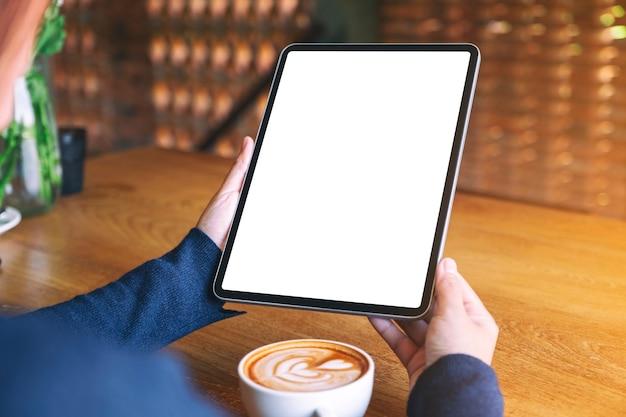 Mockup afbeelding van een vrouw met zwarte tablet pc met leeg wit scherm met koffiekopje op houten tafel