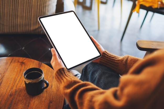Mockup afbeelding van een vrouw met zwarte tablet pc met leeg wit scherm op houten tafel