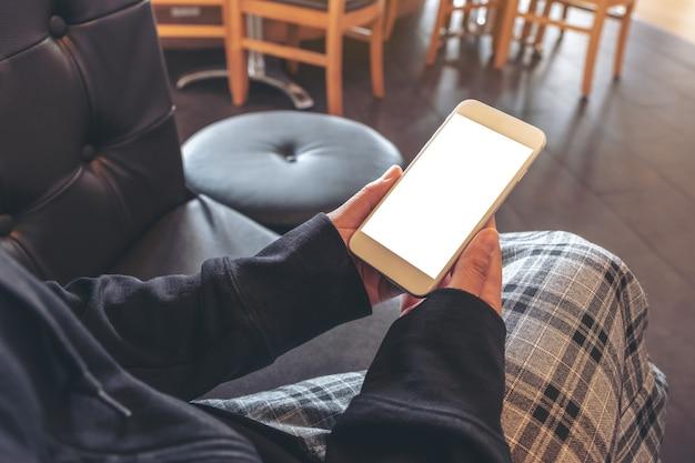 Mockup-afbeelding van handen die een witte mobiele telefoon met leeg scherm vasthouden en gebruiken terwijl u in café zit