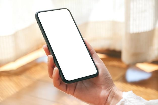 Mockup-afbeelding van handen die zwarte mobiele telefoon met leeg desktopscherm vasthouden en gebruiken