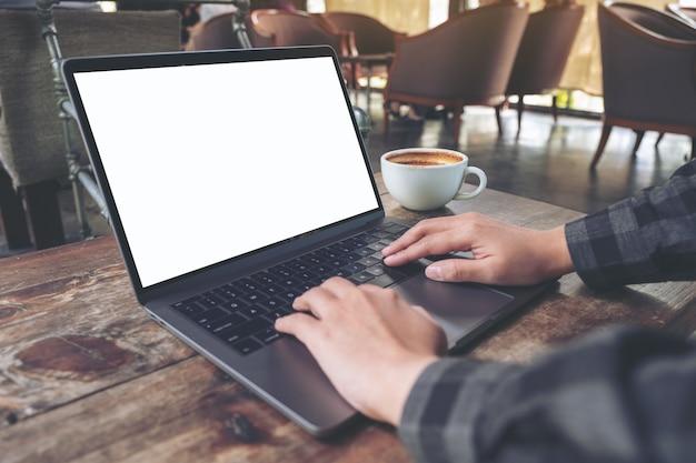Mockup-afbeelding van handen gebruiken en typen op laptop met leeg wit bureaublad met koffiekopje op houten tafel in café