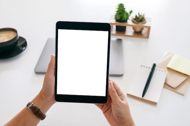 Mockup-afbeelding van handen met een tablet met een leeg wit scherm en een laptopcomputer op een houten tafel in kantoor