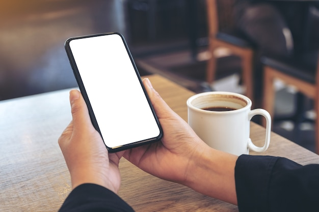 Mockup afbeelding van handen met witte mobiele telefoon met leeg scherm met koffiekopje op houten tafel in café