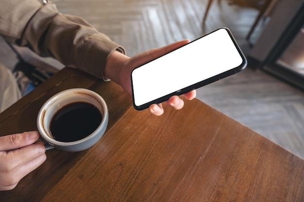 Mockup afbeelding van handen met witte mobiele telefoon met leeg scherm terwijl het drinken van koffie in café