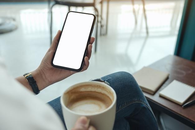 Mockup-afbeelding van handen met witte mobiele telefoon met leeg scherm tijdens het drinken van koffie