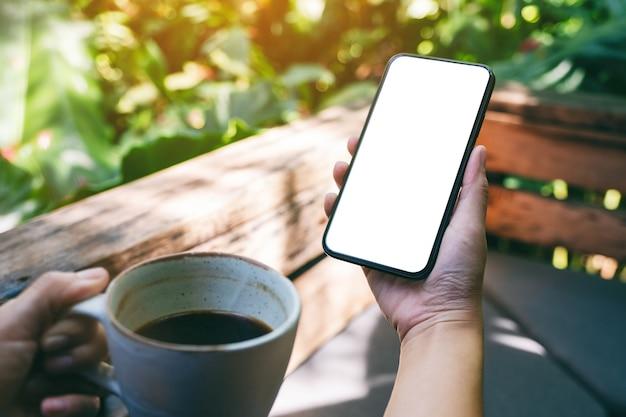 Mockup-afbeelding van handen met zwarte mobiele telefoon met een leeg desktopscherm terwijl ze buiten koffie drinken