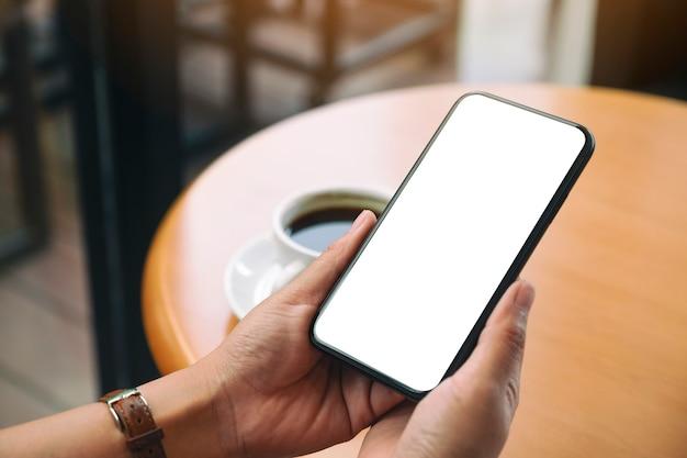 Mockup-afbeelding van handen met zwarte mobiele telefoon met leeg bureaubladscherm