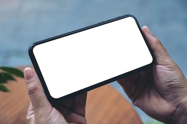 Mockup-afbeelding van handen met zwarte mobiele telefoon met leeg desktopscherm horizontaal