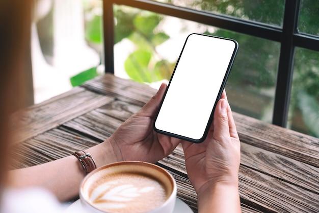 Mockup-afbeelding van handen met zwarte mobiele telefoon met leeg desktopscherm met koffiekopje op tafel