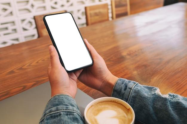Mockup-afbeelding van handen met zwarte mobiele telefoon met leeg desktopscherm met laptop en koffiekopje op tafel