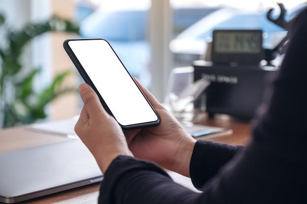 Mockup afbeelding van handen met zwarte mobiele telefoon met leeg wit scherm met laptop op houten tafel in kantoor