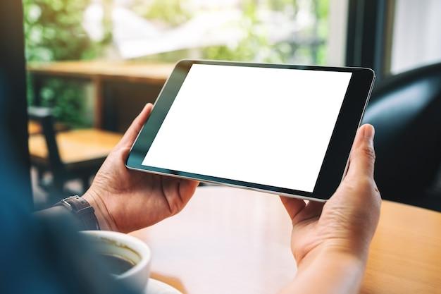 Mockup afbeelding van handen met zwarte tablet pc met leeg wit scherm met koffiekopje op houten tafel