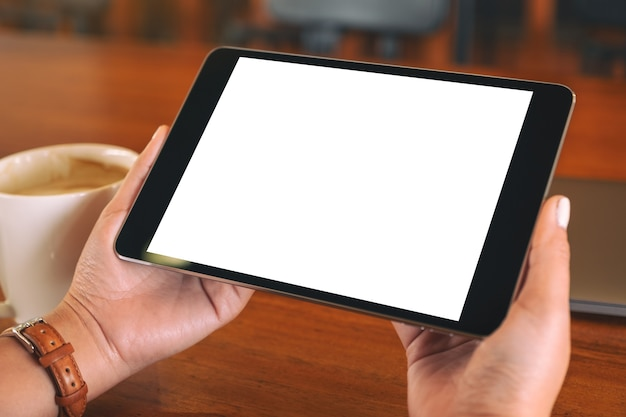 Mockup afbeelding van handen met zwarte tablet pc met leeg wit scherm met laptop en koffiekopje op houten tafel