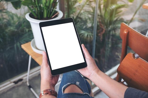 Mockup-afbeelding van handen met zwarte tablet-pc met leeg wit scherm terwijl ze in café zitten
