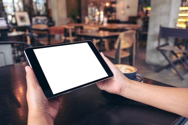 Mockup afbeelding van handen met zwarte tablet pc met leeg wit scherm