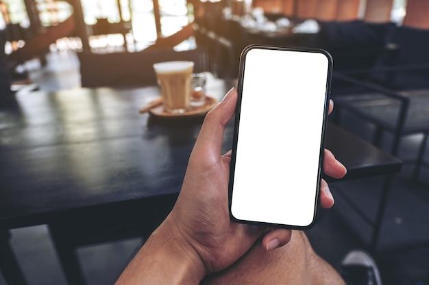 Mockup afbeelding van iemands hand met zwarte mobiele telefoon met leeg scherm met een glas koffie op houten tafel in café