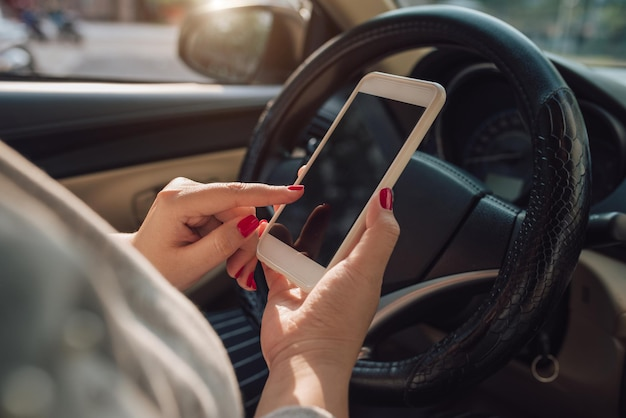 Mockup afbeelding van vrouw hand met behulp van mobiele smartphone met leeg scherm tijdens het autorijden en het verlaten van huis. uitknippad.