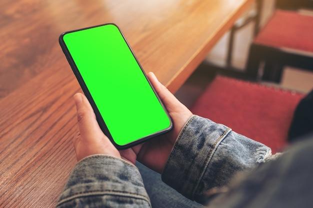Mockup afbeelding van vrouw handen met zwarte mobiele telefoon met leeg scherm in café