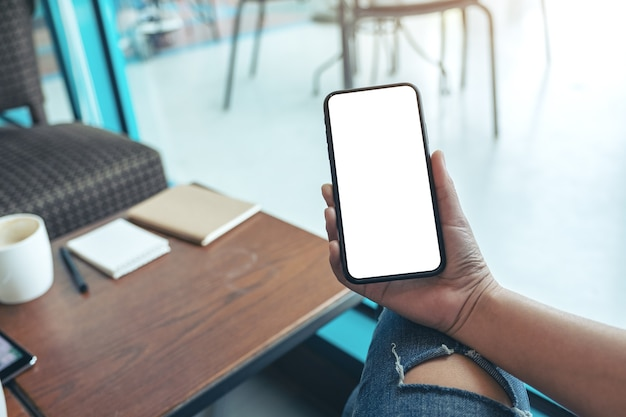 Mockup afbeelding van vrouw handen met zwarte mobiele telefoon met leeg wit scherm in café