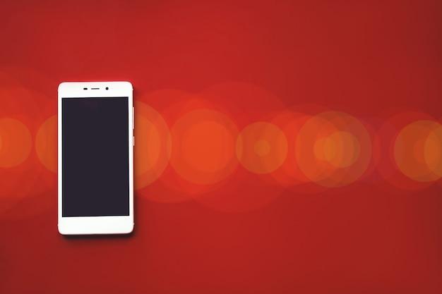 Mockup afbeelding van witte mobiele telefoon op rode achtergrond met leeg zwart scherm en bokeh.