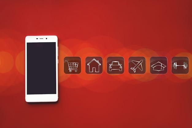 Mockup afbeelding van witte mobiele telefoon, verschillende pictogrammen voor financiële besparingen of uitgaven op rode achtergrond met leeg zwart scherm en bokeh.