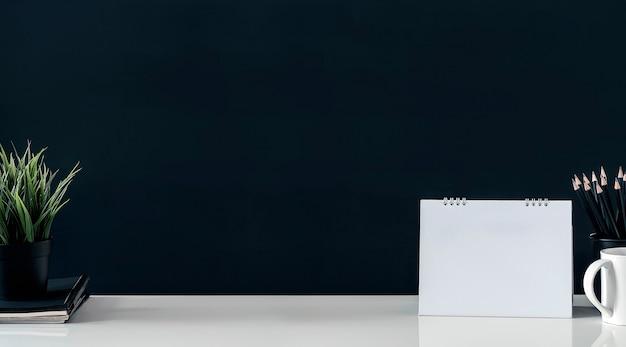 Mockup blanco pagina kalender, potlood, mok en kamerplant op witte tafel met donkere achtergrond.