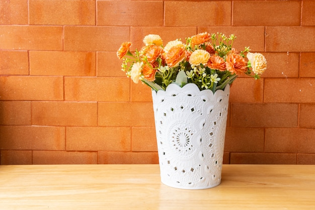 Mockup bloem bovenop een houten tafel met een bakstenen muur oranje achtergrond.