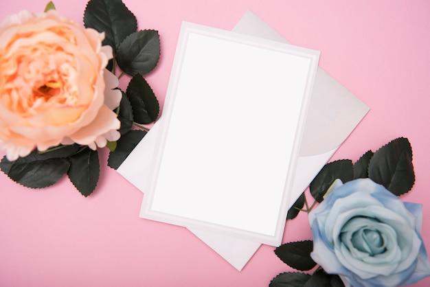 Mockup bruiloft papieren kaart en roze bloem. sjabloon voor reclame.