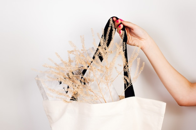 Mockup close-up van herbruikbare witte tas met zwarte handvatten met droge bloemen en krant erin o...