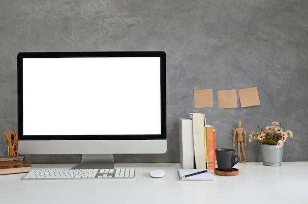Mockup-computer werkruimte, boeken, koffie en kantoorbenodigdheden met zoldermuur.