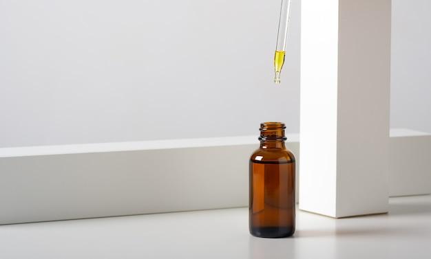 Mockup cosmetisch gezichtsserum, oliebruin glazen flesje met een pipet op een stijlvolle minimalistische witte achtergrond met geometrisch decor.