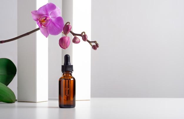 Mockup cosmetische gezichtsserum bruine glazen fles met een pipet op een stijlvolle minimalistische witte achtergrond met geometrische decor en orchideebloemen.