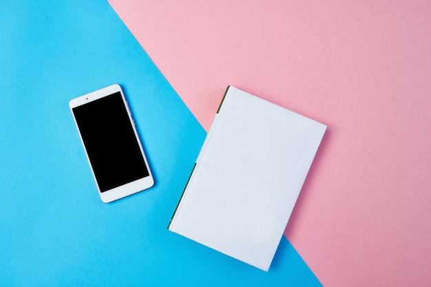 Mockup flat lag compositie met smartphone en kladblok op een blauwe en roze achtergrond.