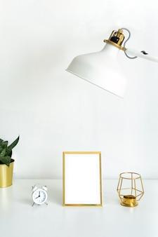 Mockup gouden fotolijst op witte tafel, bloem binnenshuis, witte wekker, gouden kandelaar en witte lamp.