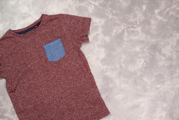 Mockup in kleur t-shirt, bovenaanzicht. t-shirt op betonnen grijze achtergrond, kopieer ruimte.