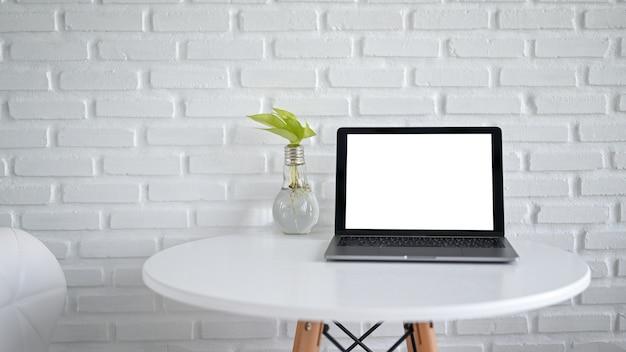 Mockup laptop scherm leeg leeg met gloeilamp vaas op witte moderne tafel in café