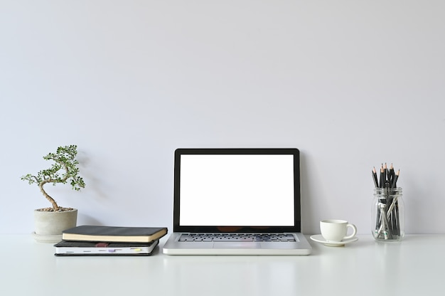 Mockup laptopcomputer en kantoorbenodigdheden en kleine bonsai op werkruimte.