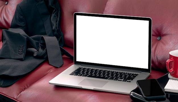 Mockup laptopcomputer op rode bank, leeg scherm voor grafisch ontwerp.