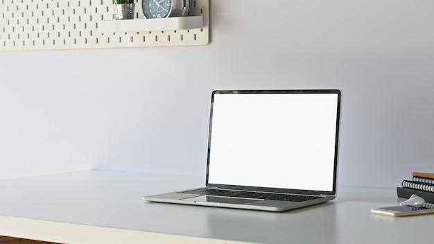 Mockup laptopcomputer op werktafel met lege schermweergave.