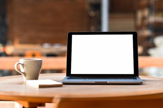 Mockup leeg scherm laptop met koffie en notebook op tafel