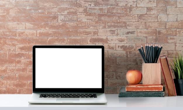 Mockup leeg scherm laptop met leveringen op witte tafel en bakstenen muur.