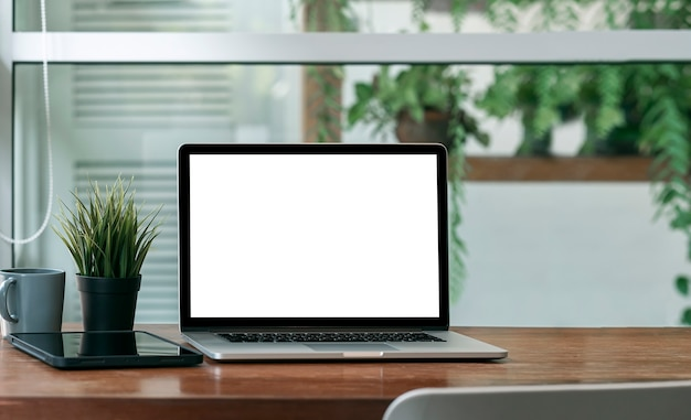 Mockup leeg scherm laptopcomputer op houten tafel met groene plant achtergrond.