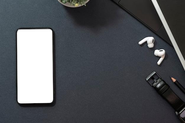 Mockup leeg scherm smartphone en gadget op zwart leer.