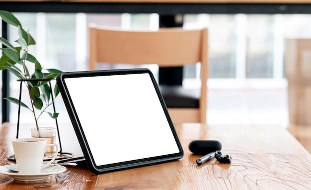 Mockup leeg scherm tablet en gadget op houten tafel met kopieerruimte.