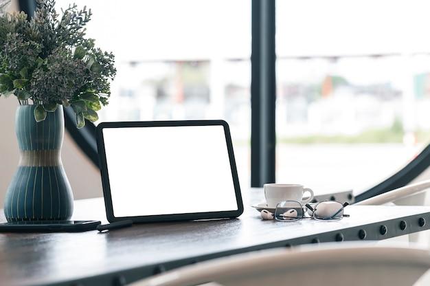 Mockup leeg scherm tablet en gadget op houten tafel.