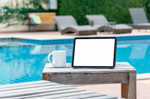 Mockup leeg scherm tablet en keramische mok op houten tafel met zwembad wazig achtergrond.