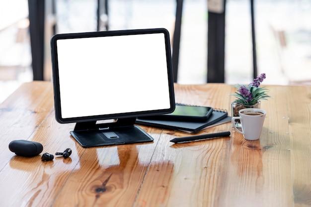Mockup leeg scherm tablet met standaard en gadget op houten tafel in co-werkruimte.