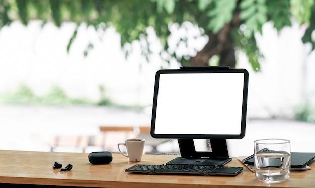 Mockup leeg scherm tablet met standaard houder en toetsenbord op houten aanrechttafel in café.
