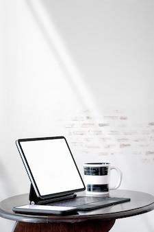Mockup leeg scherm tablet met toetsenbord en smartphone op houten salontafel in witte kamer